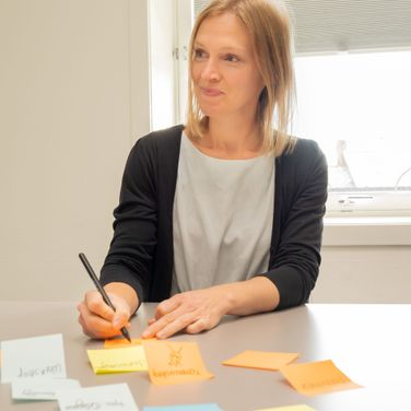 kvinne skriver på post it lapper og smiler mot siden